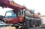 48-Tonnen-Mobilkran mit vier Achsen. Das Fahrzeug mit dem amtlichen Kennzeichen S-HP 517 ist rot lackiert, mit gelber Firmenaufschrift.
